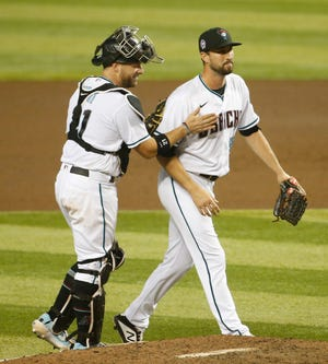 Diamondbacks' catcher Stephen Vogt (21) congratulates Stefan Crichton on the save of a 4-3 win against the Mariners at Chase Field in Phoenix, Ariz. on Sept. 11, 2020.