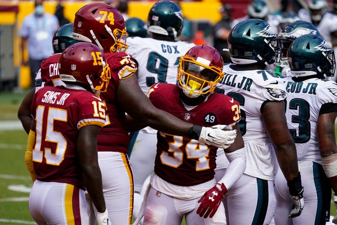 Washington Football Team running back Peyton Barber (34) celebrates his touchdown against the Philadelphia Eagles with teammates Steven Sims Jr. (15) and Geron Christian (74), during the second half of an NFL football game, Sunday, Sept. 13, 2020, in Landover, Md. (AP Photo/Alex Brandon)