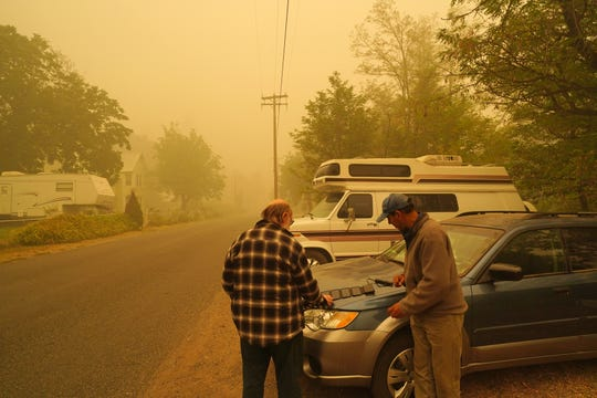 An eerie stillness hangs over the small community of Happy Camp in far Northern California on Sunday, Sept. 12, 2020, days after the Slater Fire roared through the area. The fire struck the northern part of the town. It is blamed for two deaths and the destruction of about 150 homes. These two men use solar panels to charge their phones as they wait to find out whether their homes are still standing.