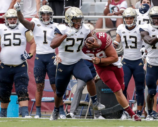 Georgia Tech running back Jordan Mason avoids a tackle by Florida State defensive end Josh Griffis during their game at Doak Campbell Stadium.