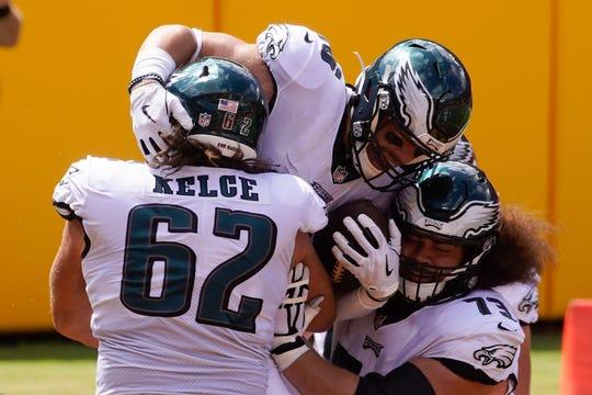 Philadelphia Eagles, Zach Ertz, tengah, merayakan touchdown dengan rekan setim center Jason Kelce (62) dan selama paruh pertama pertandingan sepak bola NFL melawan Washington Football Team Minggu, 13 September 2020, di Landover, Md. (AP Foto / Al Drago)
