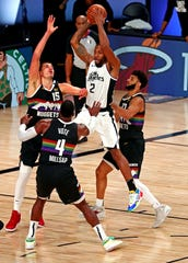 Three Denver Nuggets players surround L.A. Clippers forward Kawhi Leonard (2) during the third quarter of Game 6.
