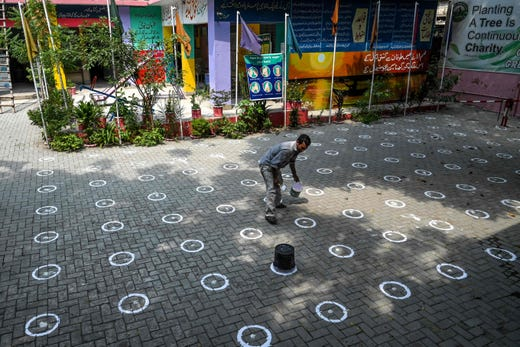 A worker draws marks on the ground for social distancing at a school in Lahore on Sept. 13, 2020, following the government's announcement to reopen educational institutes starting from September 15, nearly six months after the spread of the COVID-19 coronavirus.