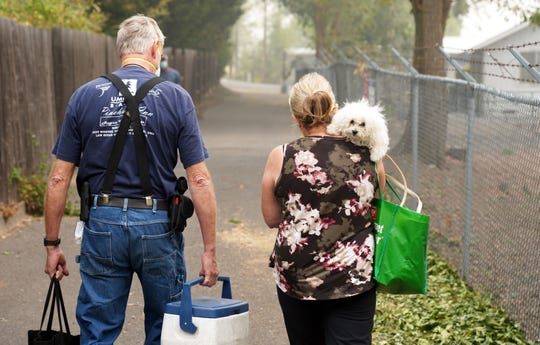 Scott Coash, left, carries a cooler, hand sanitizer and a handgun as he walks into his evacuated neighborhood with his wife Cindy and their dog Bella, near Medford, Oregon, following the passage of the Almeda fire.