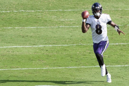 Baltimore Ravens quarterback Lamar Jackson (8) looks to throw on the run during the second half against the Cleveland Browns  at M&T Bank Stadium.