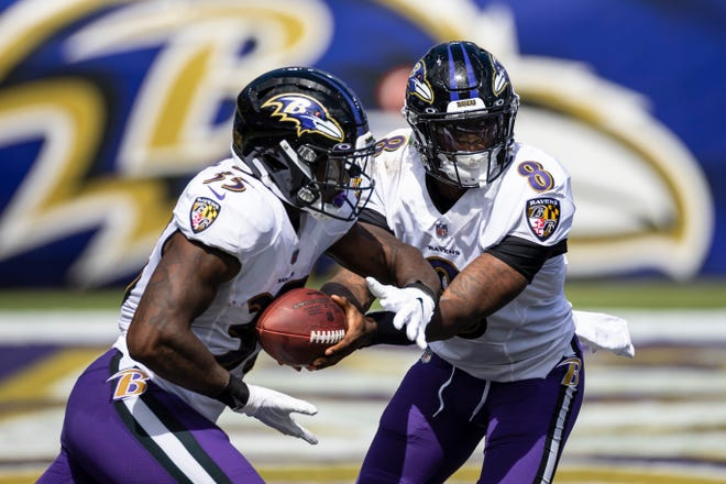 Lamar Jackson #8 of the Baltimore Ravens hands the ball off to Gus Edwards #35 against the Cleveland Browns during the first half at M&T Bank Stadium on September 13, 2020 in Baltimore, Maryland.