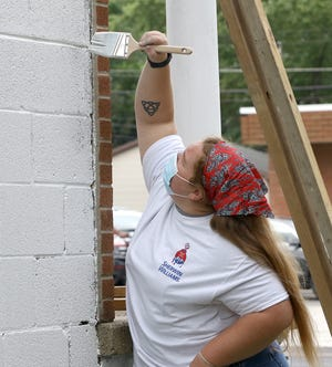 Mount Union graduate Destanee O'Neil, from Beloit, applies a white primer paint to the exterior of the former Hometown Carpet & Flooring store at 1006 S. Arch as the Alliance Area Habitat for Humanity prepares to open a ReStore and offices on Saturday, Sept. 12, 2020.