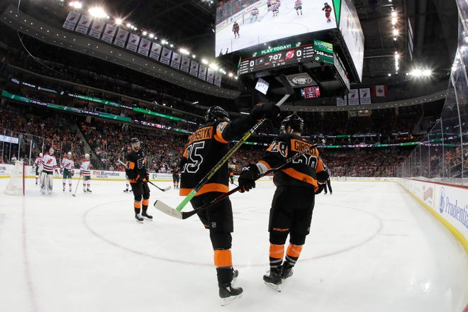 The Flyers' James van Riemsdyk, left, celebrates with teammate Claude Giroux after van Riemsdyk scored a goal against the Devils.