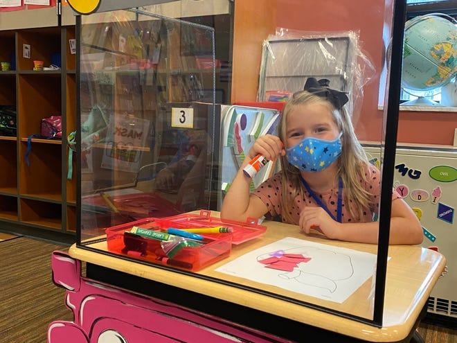 "Kindergartener Caroline Massaro sits at her pink ""Jeep"" desk. Jessica Morgan, a kindergarten teacher at Beaver Area School District, created ""Jeeps"" out of her student's desks to add a bit of fun and flair to social distancing protocols due to COVID-19."