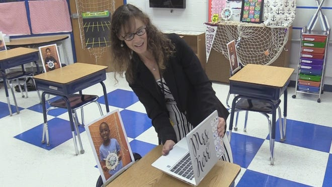 Hilton Head Island School for the Creative Arts teacher Jennifer Friend-Kerr shows her fourth-grade class desks with their pictures resting on top of the chairs. The Beaufort County School District started the year with online classes because of the coronavirus pandemic.