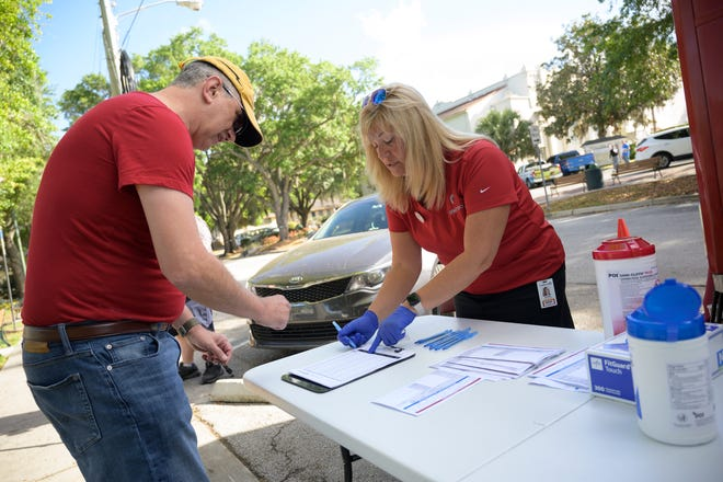 A man signs up to donate blood at OneBlood Big Red Bus in Mount Dora on Friday, March 20, 2020. [Cindy Peterson/Correspondent]