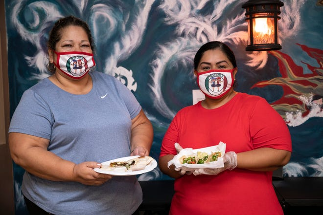 Diana Haro and owner Lily Salazar hold up their signature tacos and quesadillas at Taco Chics in Eustis. [Cindy Peterson/Correspondent]