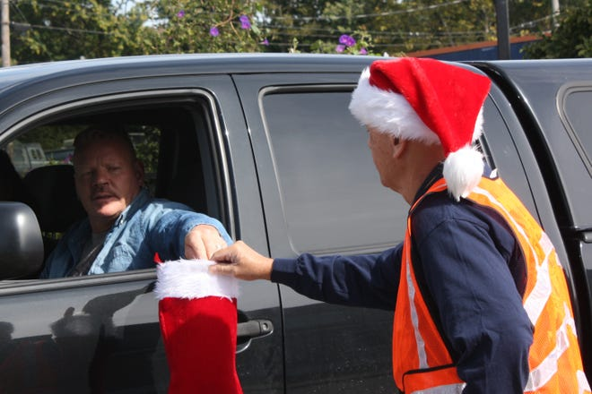 Chuck Fair, president, working to Stuff Santa's Stocking and raise funds for the club's Christmas food basket service project.