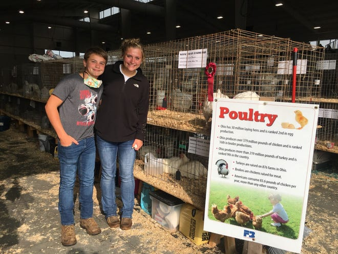Mason and Olivia Haines, students at Green Local and members of the Smithie Whiz Kids 4-H Club, smile for a photograph inside the Wayne County Fair Event Center, where they showed their chickens in the Poultry Show on Monday. Olivia placed second for her market chickens.