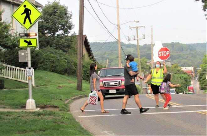 Mike and Stephanie Ruhl and their son Jakob accompany daughter Lydia across East Jackson Street in front of Millersburg Elementary School as crossing guard Angie Zimmerly holds up the stop sign to control traffic. The village of Millersburg has added new flashing lights at the crosswalks at three locations around the school for the safety of the children crossing the streets. Drivers are reminded that when those lights are flashing, pedestrians have the right of way in the crosswalk.