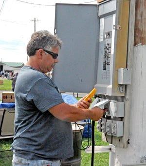 Marlin Questel, Wayne County Fair electrician, checks out a fuse box on the fairgrounds.