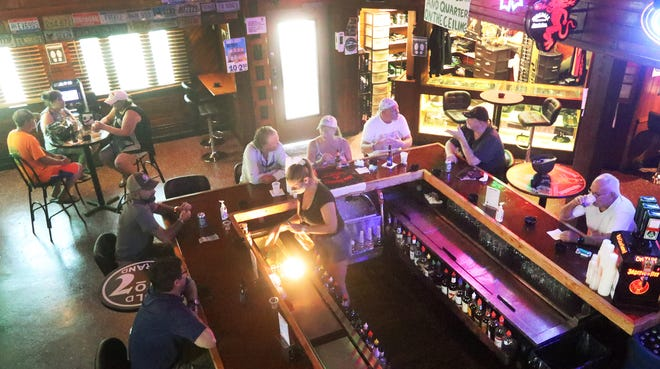Several people gather around the bar at Froggy's Saloon on Main Street in Daytona Beach, Monday September 14, 2020. Bars in Florida were permitted to reopen Monday at 50% capacity, following months of closure during the coronavirus pandemic.
