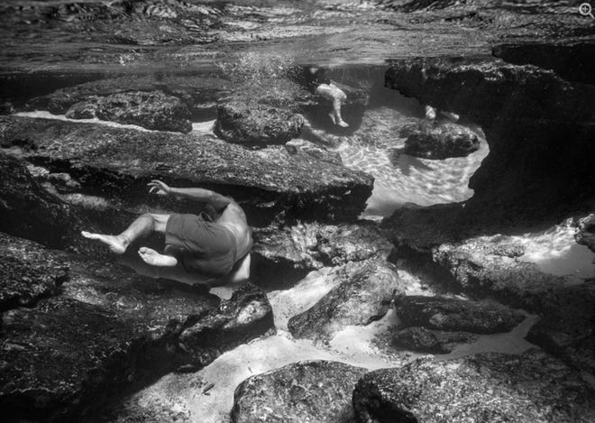 Swimmers explore the rocky bottom at DeLeon Springs, in a photo by Alexander Diaz featured in the Submerged exhibit at The Hand Art Center in Stetson University.