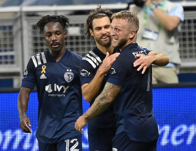 Sporting Kansas City forward Johnny Russell, right, celebrates with teammates Graham Zusi, center, and Gerso (12) after scoring a goal against Minnesota United on a pass from Zusi during the second half Sunday at Children's Mercy Park. Sporting went on to a 1-0 win to vault back into first place in the MLS Western Conference standings.