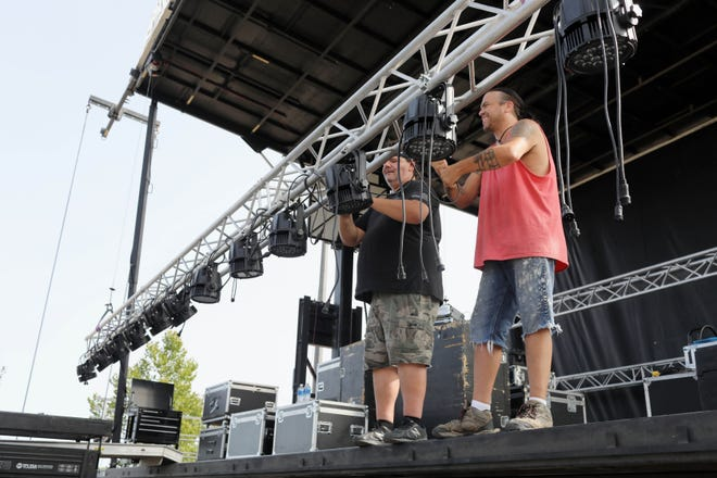 Brad Timmerman and Travis Perry, with Thunder and Lightning Productions, rig the lights for the outdoor concert stage Monday in front of Memorial Auditorium. Civic Music will hold its opening concert at 7 p.m. Tuesday in the parking lot of the Burlington Memorial Auditorium with Six Appeal and the George Maurer Quartet. Burlington Heritage Days will continue the music Wednesday through Saturday.