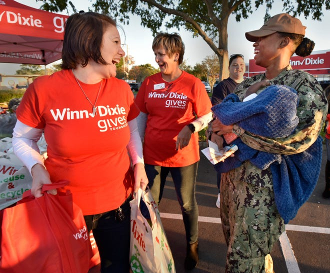 Winn-Dixie employee Margie Ryals (left) carries food given to Petty Officer 3rd Class Asia Lee and her son Jayden Rhys, 4 months, at a 2019 giveaway sponsored by the grocer and Feeding Northeast Florida. which will partner on another food pantry event Tuesday, Sept. 15.