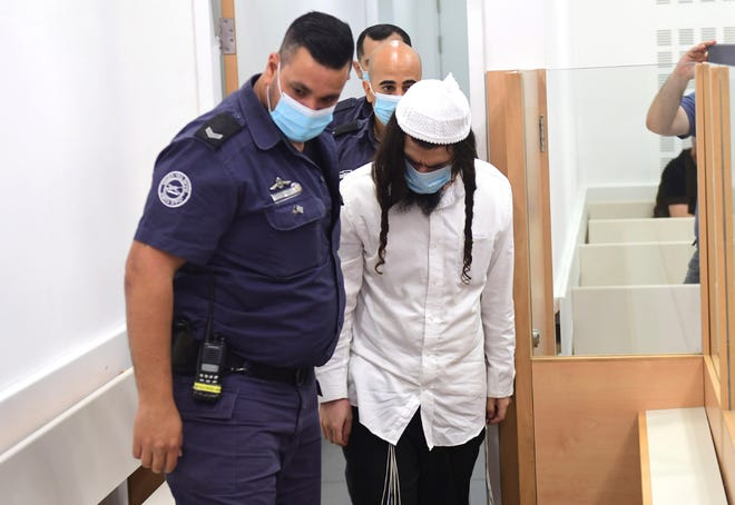 Israeli Jewish extremist Amiram Ben-Uliel arrives at a district court for a verdict in Lod, Israel in May. On Monday,  an Israeli court handed down three life sentences to Ben-Uliel, convicted in a 2015 arson attack that killed a Palestinian toddler and his parents.