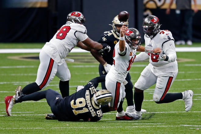 Tampa Bay Buccaneers quarterback Tom Brady (12) tries to throw as he is brought down by New Orleans Saints defensive end Trey Hendrickson (91) in the first half Sunday in New Orleans. He was called for intentional grounding on the play.