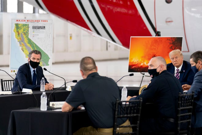 President Donald Trump participates in a briefing on wildfires with Calif. Gov. Gavin Newsom, left, at Sacramento McClellan Airport in McClellan Park, Calif., on Monday.