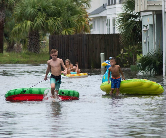 Landon Suarez and Landon Campbell turn the flooded parking lot of the Bahia-Paz condos into a waterpark on Monday in Pensacola Beach. Hurricane Sally is expected to bring up to 15 inches of rain to the western Florida Panhandle.