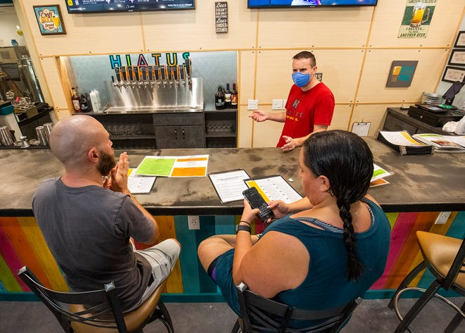 Adam Chapman, center, takes an order from customers at the Hiatus Brewing Co.'s bar on Monday. Florida allowed most bars to reopen on Monday at 50% capacity. Patrons like TIm Rehak, left, and his wife, Isabel, were excited to return to the bar.