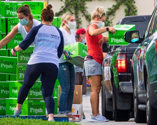 A driver watches as volunteers for Feeding South Florida load food into vehicles during the weekly drive-up distribution at the Palm Beach Outlets Monday in West Palm Beach. 1,000 families were provided with approximately a one-week supply of a protein, fresh produce, eggs, milk, and other essential goods on a first come, first served basis. Workers included many individual volunteers, along with groups from the Junior League of the Palm Beaches and the Hospitality Team of Palm Beach. The program welcomes anyone who needs food. [LANNIS WATERS/palmbeachpost.com]
