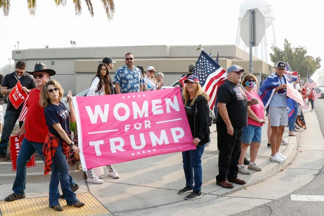 Supporters of President Donald Trump gather at the corner of Peacekeeper Way and Luce Avenue for the arrival of the president at McClellan Park airfield in Sacramento on Monday. The president came to California for a briefing on the the wildfires in California. [SARA NEVIS/FOR THE RECORD]