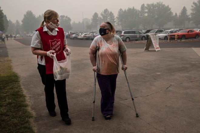 Mary Thomson, left, from Phoenix gets assistance from Salvation Army officer Tawnya Stumpf at the evacuation center set up at the Jackson County Fairgrounds on Saturday in Central Point.