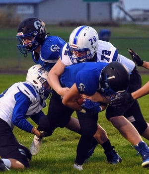 Collins-Maxwell's Brayden Bartleson brings down Colo-NESCO's Andrew Grover during the first quarter of the Spartans' 34-30 loss to the Royals Friday in Colo.