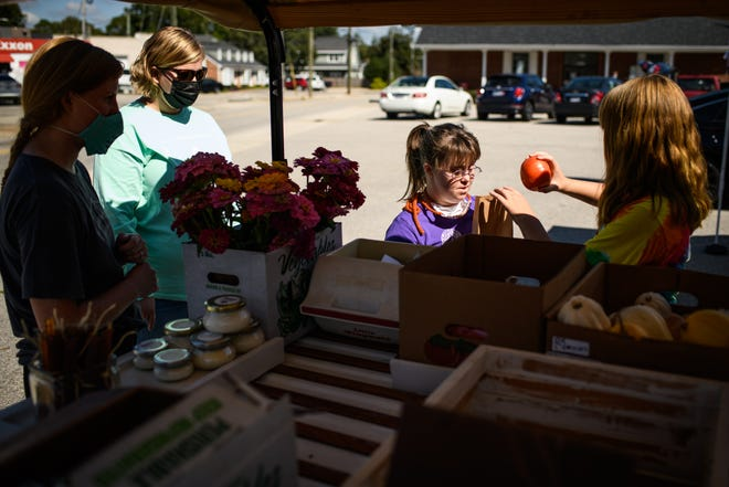 Rachel Powers, second from right, helps customer Abigail Dew bag tomatoes at the Kindred Ministries produce stand on Sept. 14 in the parking lot of the Haymount Post Office. It's one of the organizations that minister and doctor Scott Cameron works with.