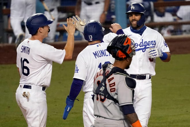 Los Angeles Dodgers' Chris Taylor, right, celebrates with Will Smith, left, and Max Muncy after hitting a three-run home run against the Houston Astros during the eighth inning Sunday, Sept. 13, 2020.
