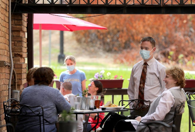 General manger Lucas Maggard talks with customers in the outdoor dining area at Stone Arch Brewpub.