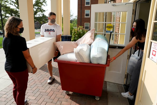 Kirsten Tibbitts, a second-year student, far right, leads her mom, Heather, and dad, Jeff, into Minnich Hall as she moves in, Monday, Sept. 14, 2020, at Miami University in Oxford, Ohio.