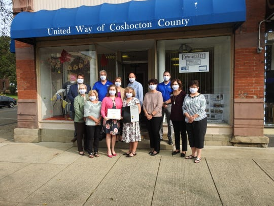 Employees, board members and local dignitaries with proclamations presented by State Sen. Jay Hottinger and Tim Ross from the office of Congressman Bob Gibbs honoring the local organization's 80 years in the local community in front of the United Way of Coshocton County office on Main Street.