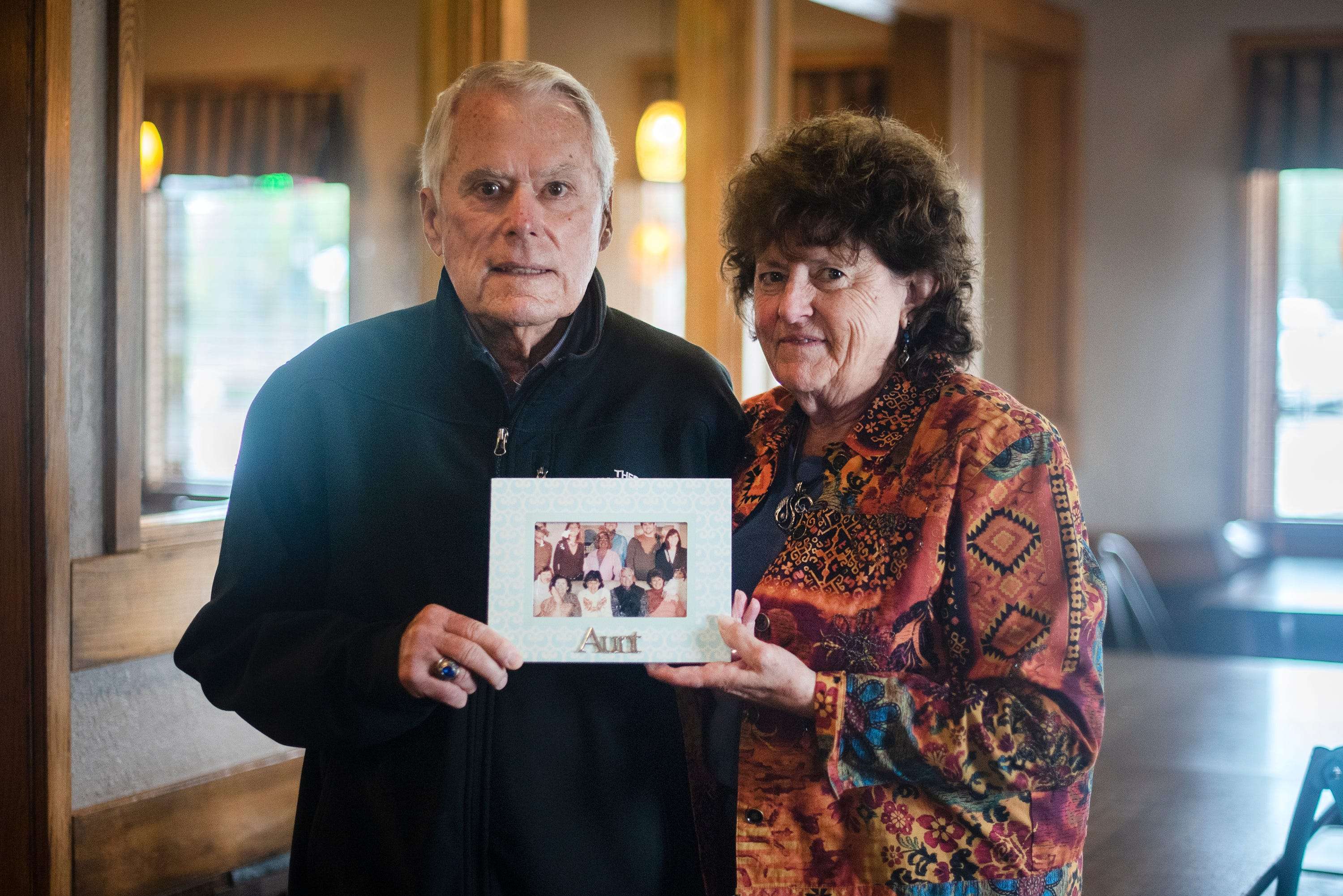 Walt Bussey and his wife, Cindy, hold a portrait of Walt's aunt Katie Jacobs, who died of COVID-19.