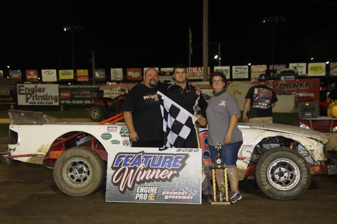 Clyde's Austin Black, middle, celebrates in victory lane with his parents, Kenny Black, and Wendy Black, right. It was Black's first career win at Fremont Speedway.
