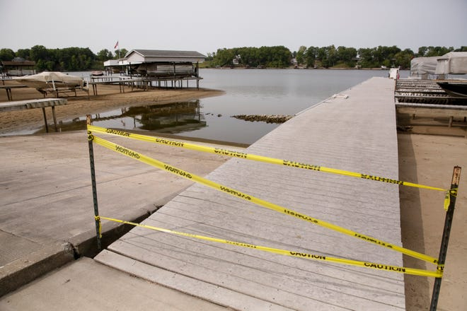 Caution tape is stretched across the entrace to a dock at Tall Timbers Marina as water levels continue to lower on the Tippecanoe River and Lake Freeman, Monday, Sept. 14, 2020 in Monticello.
