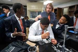 Students react to what they see under a microscope in Matthew Howell's science class at the W.E.B. DuBois Academy. Oct. 17, 2019.