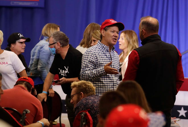 Donald Trump supporters, some wearing masks and others not, chat Monday before the arrival of Vice President Mike Pence at a campaign rally in Janesville. Pence was touring the Midwest touting the accomplishments of the Trump administration.
