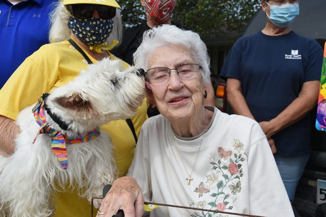 Doris Nichele, surrounded by friends, gets an 80th birthday kiss from a well wishing four legged friend.