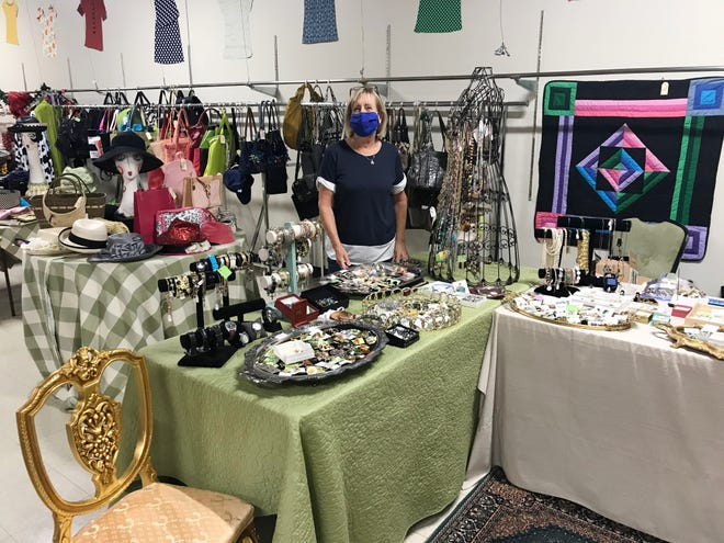 """Claudia Kornmeyer shows off some of the jewelry and handbag items available at the Ladies of Charity """"Stuff Galore"""" sale."""