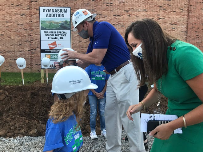Poplar Grove Elementary Principal Alisha Erickson and Nabholz Project Executive Adam Seiter fit hard hats on students Norah Holiday and Roberto Mendez prior to the groundbreaking of the Poplar Grove School gym.