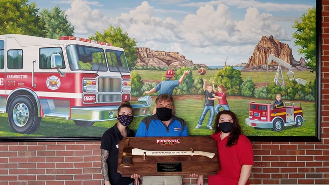 From left to right: Assistant Manager Taylor Dewees, Franchisee Darin Fitzgerald and General Manager Charity Morales showcasing the Axe Award in front of Firehouse Subs Farmington's mural.