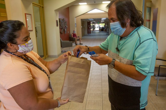 April Cruz, community health testing and education manager and Jose De La Cruz, testing coordinator, both at Desert AIDS Project in Palm Springs fill a bag with condoms that are given free of charge to the public.