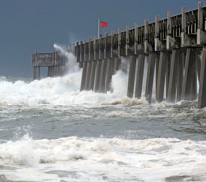 High seas and rough surf pound the Pensacola Beach fishing pier as Hurricane Sally churns in the Gulf of Mexico on Monday.